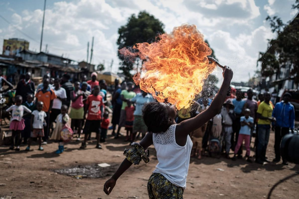 A member of Kenyan acrobat group Kibera Messenger breathes fire during a performance for filming in Kibera, Nairobi, on March 7, 2018. PHOTO: AFP