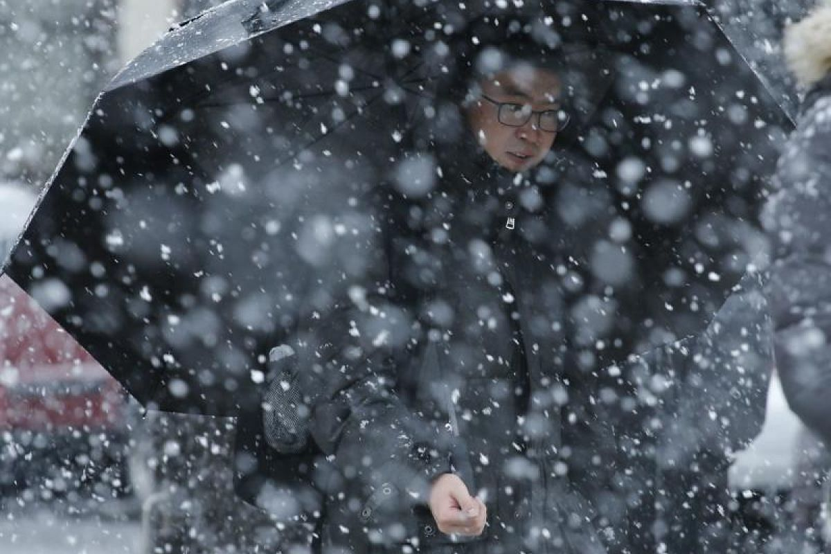 A man holds an umbrella as snow falls while the winter storm Quinn approaches New York City on March 7, 2018 in Hoboken, New Jersey.
