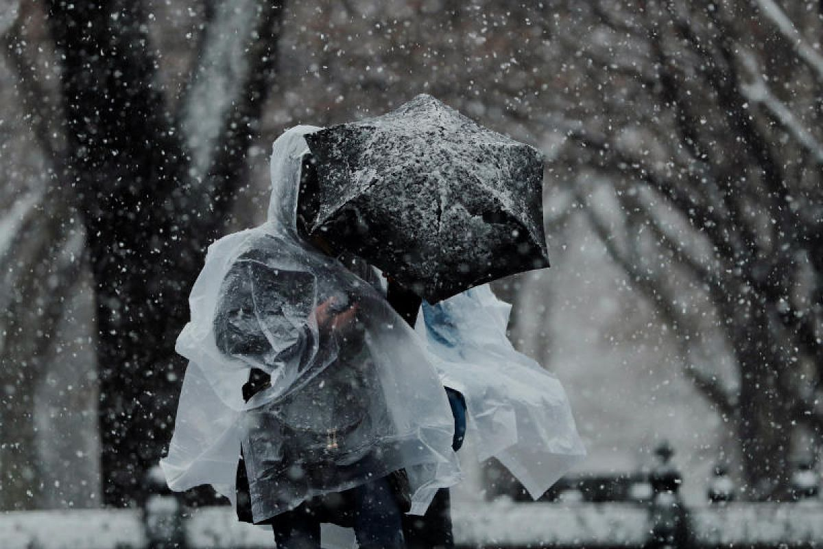 Pedestrians walk through Central Park during a snow storm in New York, US on March 7, 2018.