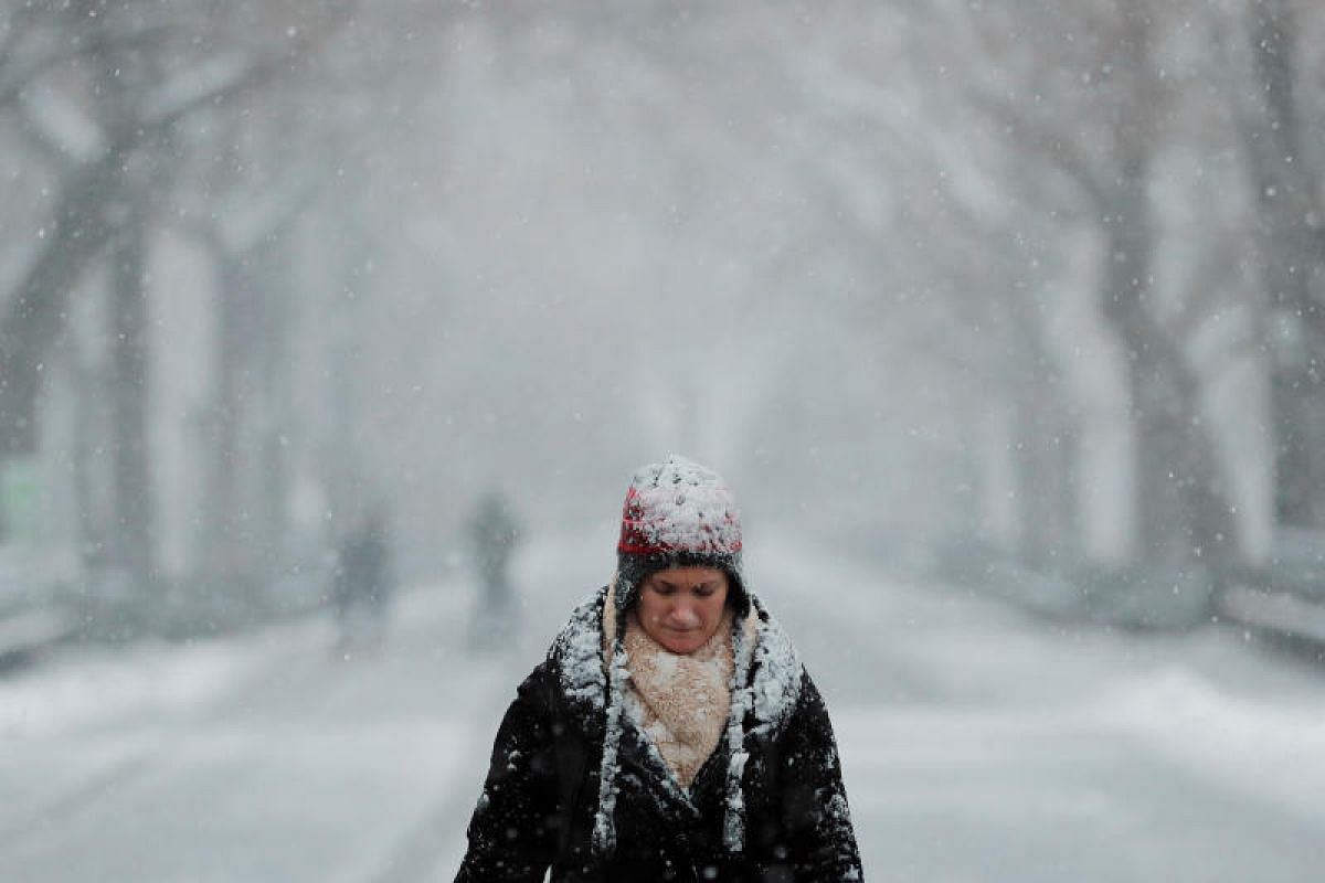 A pedestrian walks through Central Park during a snow storm in New York, US on March 7, 2018.