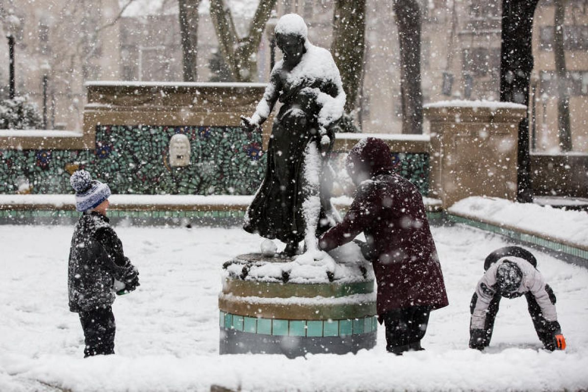 Residents play in the snow at Rittenhouse Square Park during Winter Storm Quinn in Philadelphia, Pennsylvania, US on March 7, 2018.