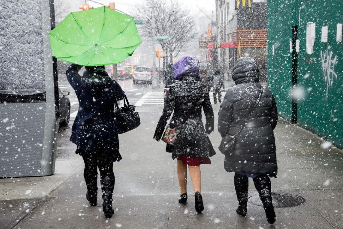 Women make their way along Broadway in upper Manhattan during a snowstorm on March 7, 2018.