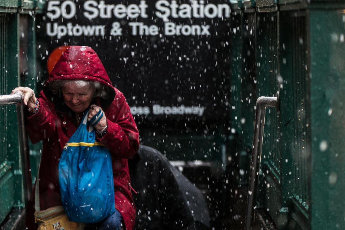 A woman makes her way out of the subway station at West 50th Street and Broadway in midtown Manhattan during a snowstorm on March 7, 2018.