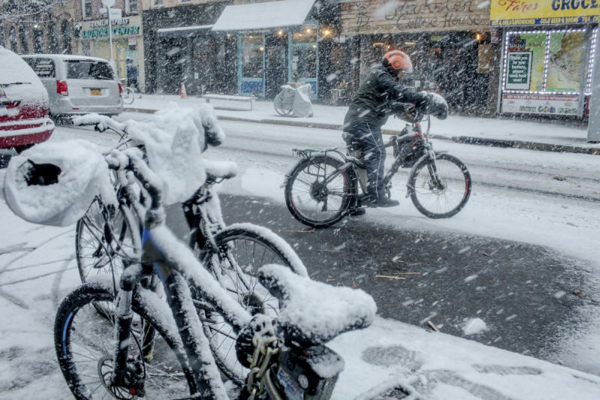 A delivery man gets on his motorized bike during a winter storm in the Crown Heights neighborhood of Brooklyn, on March 7, 2018.