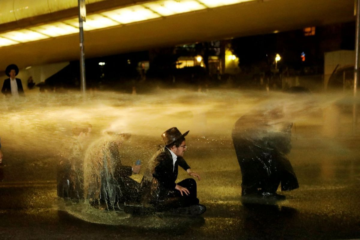 Israeli ultra-Orthodox Jewish men sit as a water canon is activated during a protest against the detention of a member of their community who refuses to serve in the Israeli army, in Jerusalem March 8, 2018. PHOTO:REUTERS