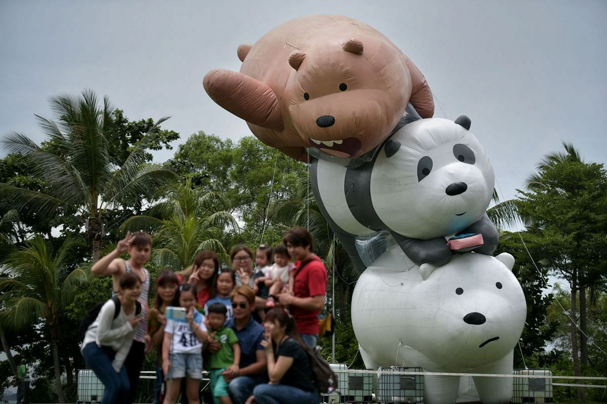 """Grizz, Pan Pan and Ice Bear, characters from Cartoon Network's """"We Bare Bears"""", form a 50-foot tall, three-layer inflatable bearstack as tourists from Taiwan take a wefie on 7 Mar 2018. Over 300 inflatable bears will be displayed at  Sentosa's Pala"""
