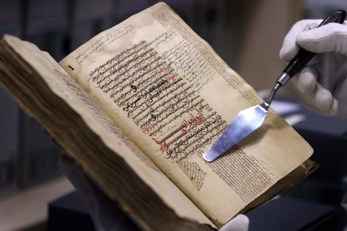 A photo released on March 9, 2018, shows Father Najeeb Michaeel displaying a page of an old book at the Oriental Manuscript Digitisation Centre (CNDO) in Arbil, the capital of Iraq's autonomous northern Kurdish region, on March 1, 2018. PHOTO: AFP