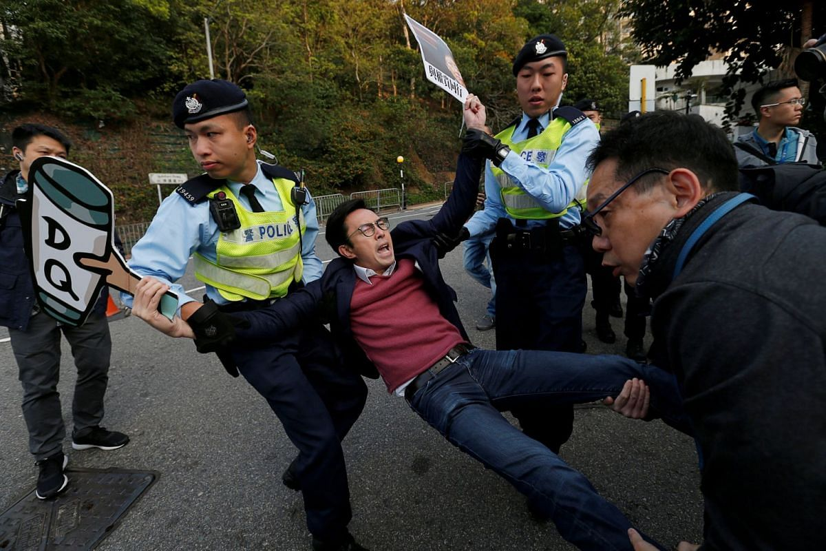 A pro-democracy protester against the disqualification of lawmakers is taken away by the police before Hong Kong Chief Executive Carrie Lam arrives to vote during a Legislative Council by-election in Hong Kong, China March 11, 2018. PHOTO: REUTERS