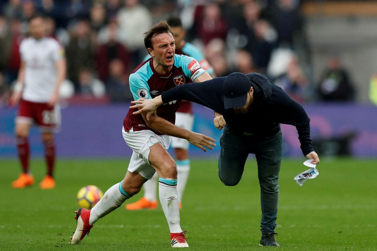 West Ham United's Mark Noble clashes with a fan who invaded the pitch during the Premiere League soccer match between West Ham United and Burnley at London Stadium, London, Britain on March 10, 2018. PHOTO: ACTION IMAGES VIA REUTERS