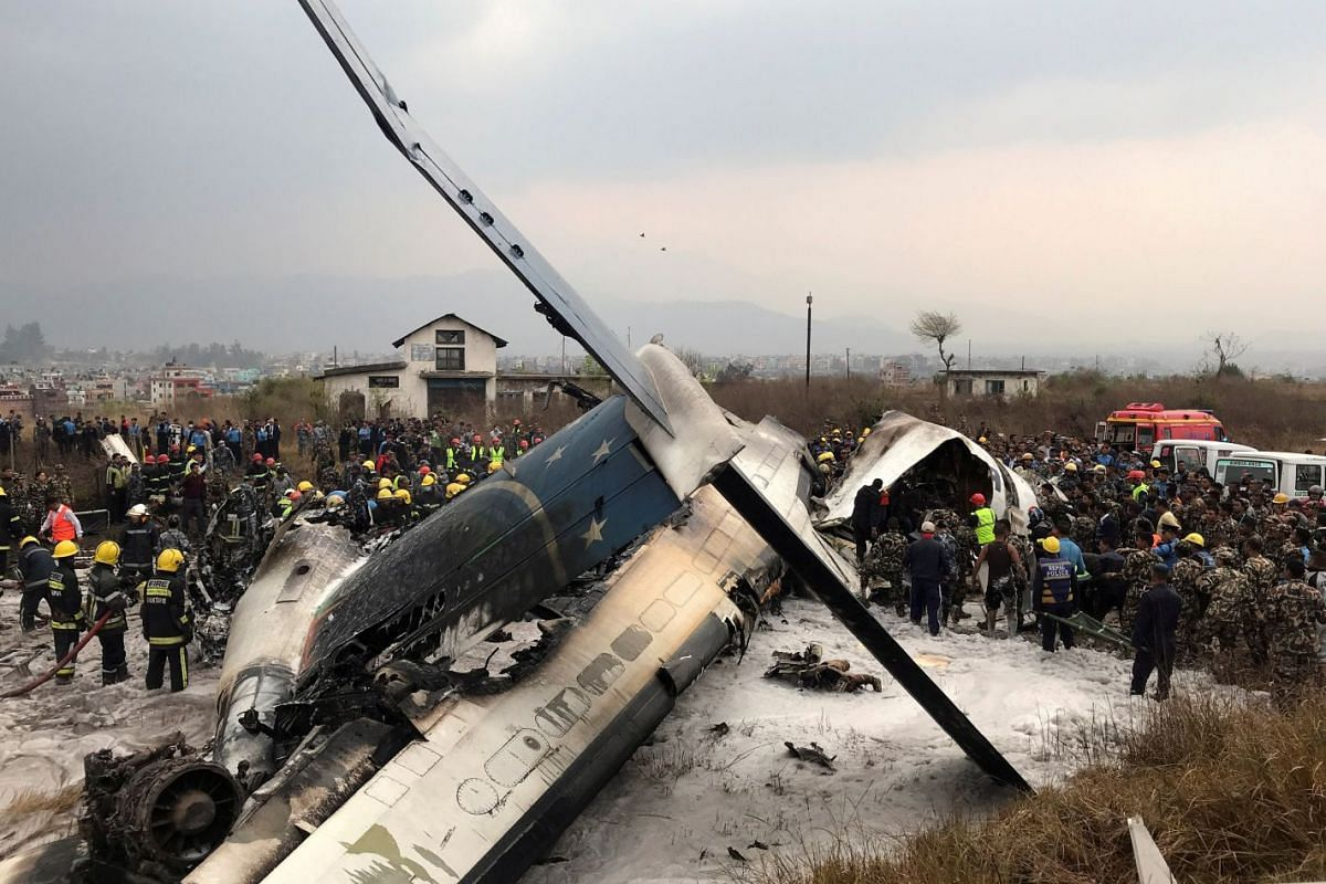 Wreckage of an airplane is pictured as rescue workers operate at Kathmandu airport, Nepal March 12, 2018. PHOTO: REUTERS