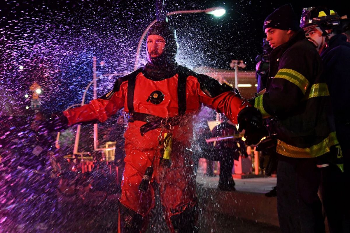 A FDNY rescue diver is hosed off with fresh water after pulling victims from a submerged helicopter after it crashed into the East River in New York, U.S., March 11, 2018. PHOTO: REUTERS
