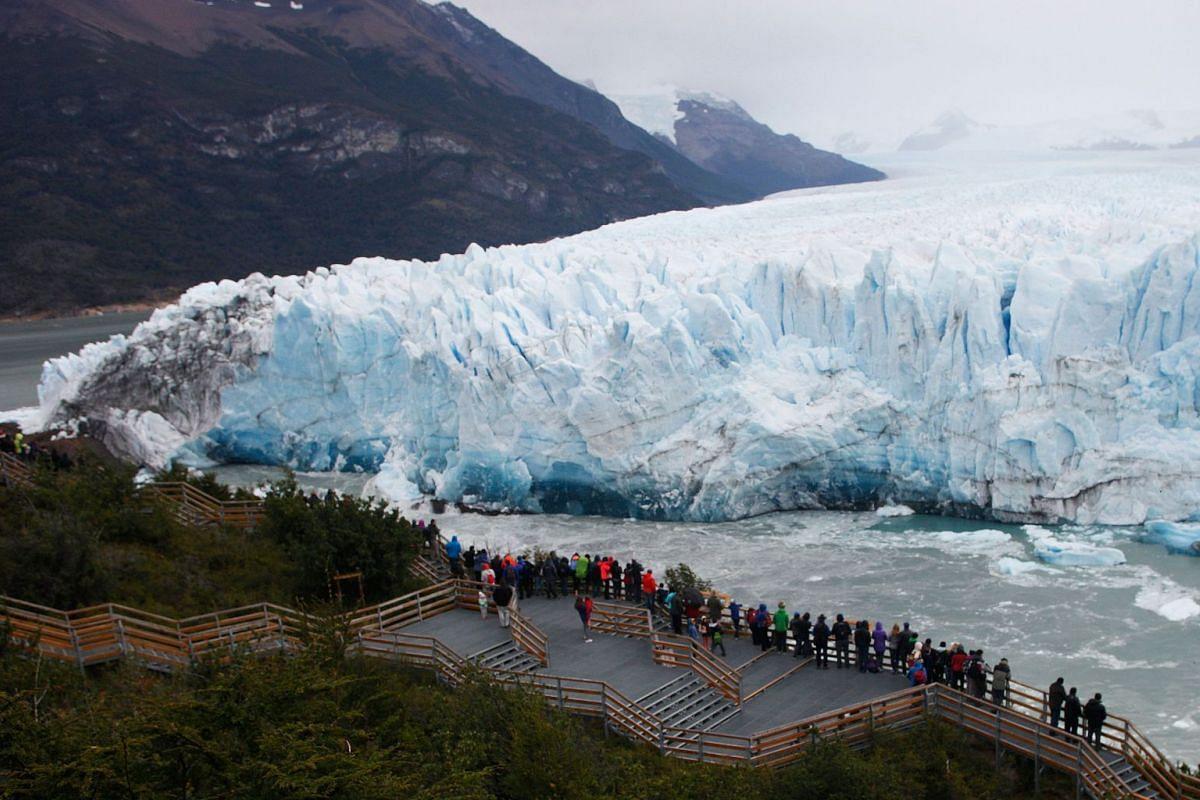 Tourists watch the Perito Moreno Glacier, at Los Glaciares National Park, near El Calafate in the Argentine province of Santa Cruz, on March 10, 2018. PHOTO: AFP