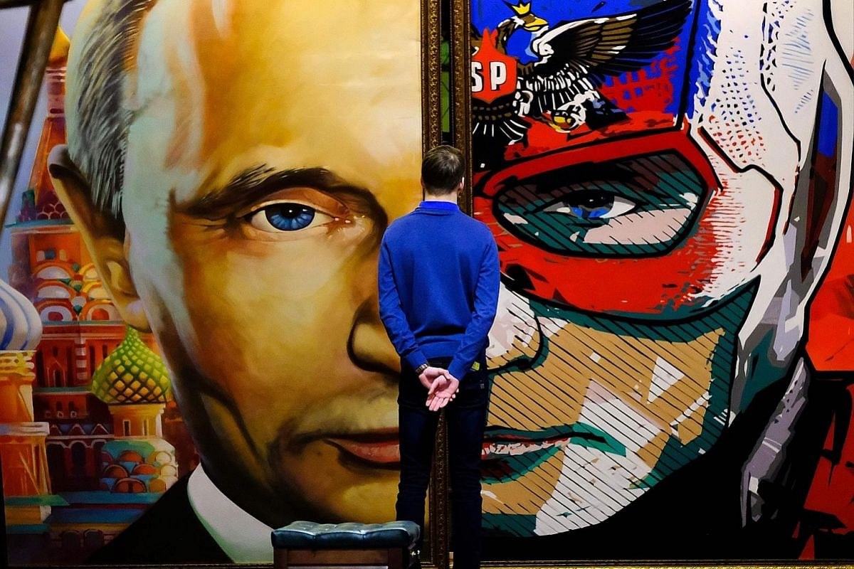 """Campaign activists verifying signatures in support of Mr Putin as a candidate at his election campaign office in Moscow in January. On display at the SUPERPUTIN exhibition in Moscow's UMAM museum is this painting depicting """"superhero"""" Russian Preside"""