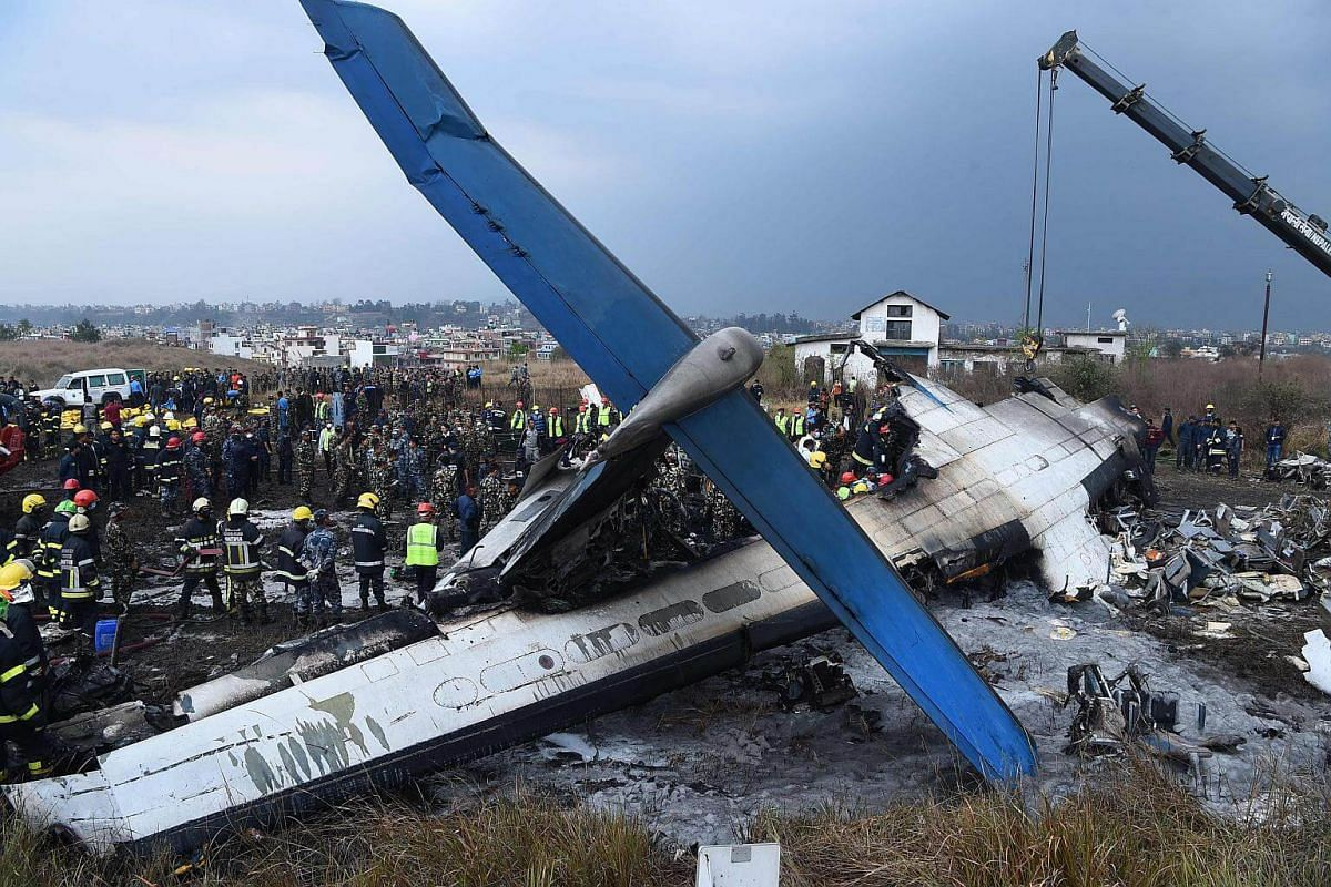 Nepali rescue workers gather around the debris of an airplane that crashed near the international airport in Kathmandu on March 12, 2018.