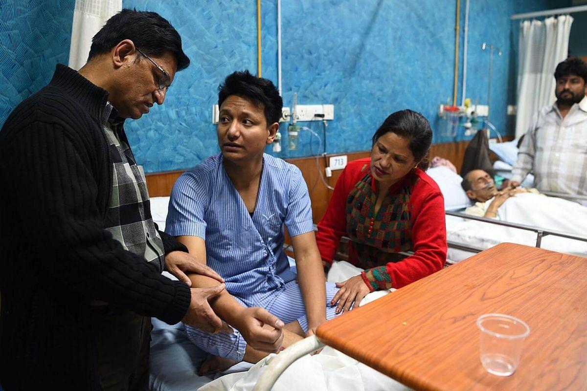 Plane crash survivor Sanam Shakya (centre) talks with his parents at the Norvic Hospital in Kathmandu on March 12, 2018.