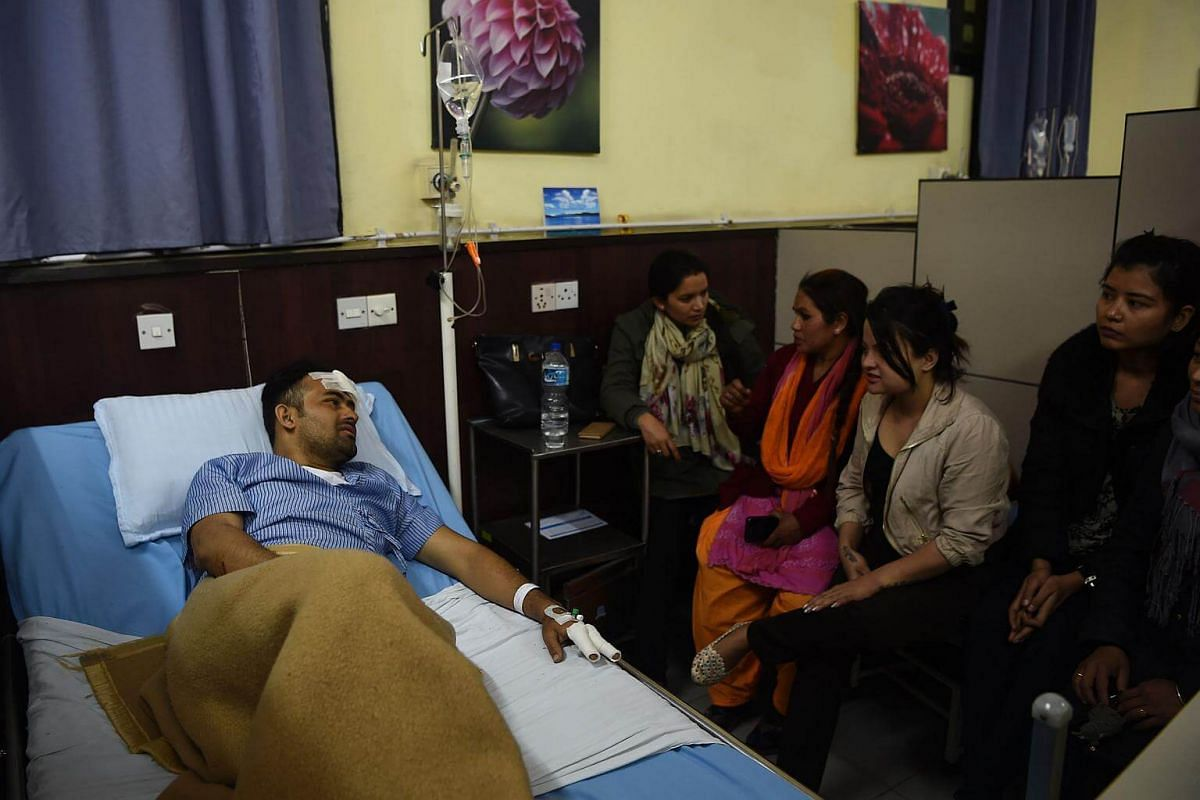Plane crash survivor Basanta Bohara (left) talks with his friend and family at the Norvic Hospital in Kathmandu on March 12, 2018.