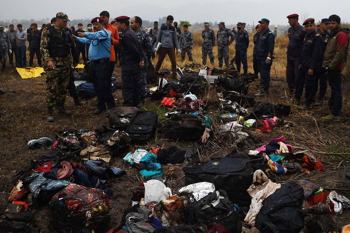 The belongings of passengers traveling on an airplane that crashed lie at the crash site near the international airport in Kathmandu on March 12, 2018.