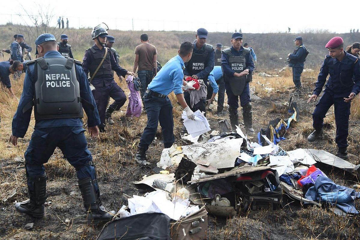 Nepali rescue workers search through the debris of an airplane that crashed near the international airport in Kathmandu on March 12, 2018.