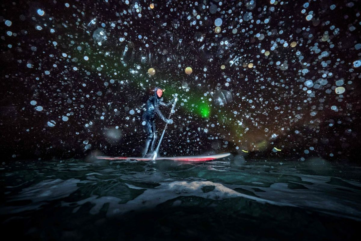 A photo released on March 14, 2018 shows Myrtille Heissat from France riding a SUP (Stand Upp Paddle) under Northern Lights, on March 8, 2018 in Unstad northern Norway, Lofoten islands, within the Arctic Circle. PHOTO: AFP