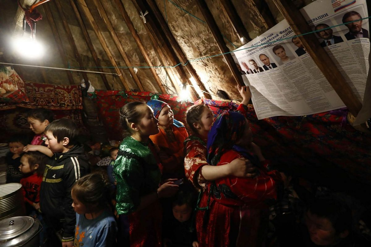 A photo released on March 14, 2018 shows members of a local indigenous community gathering near a broadsheet with information about presidential candidates inside a yurt tent during the early voting in remote areas ahead of the presidential election