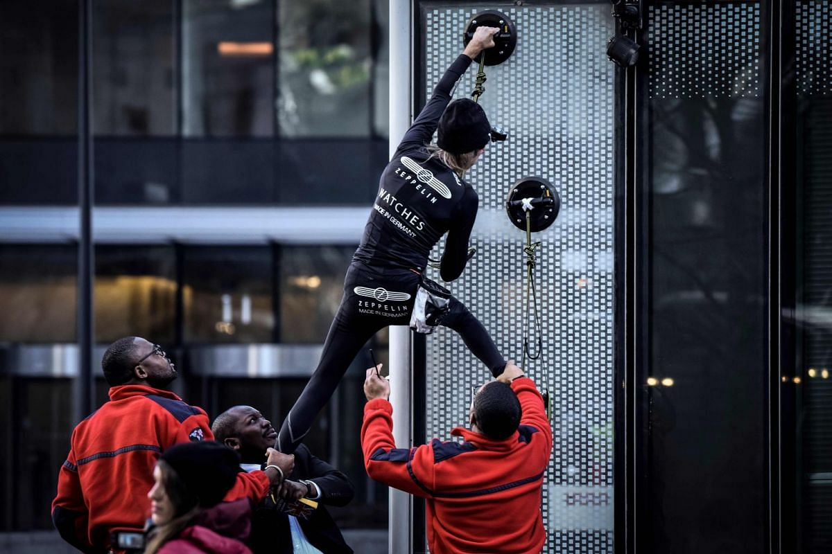 Alain Robert, the French urban climber dubbed Spiderman, is grabbed by security guards preventing him to climb a building hosting the headquarters of French energy giant Engie at La Defense business area, in Paris on March 14, 2018. PHOTO: AFP