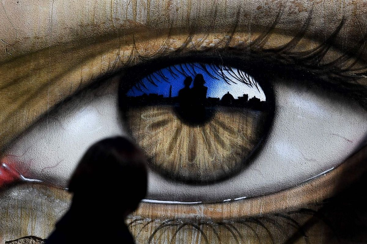 A girl walks past an eye drawn by British street artist My Dog Sighs in Rome on March 14, 2018. PHOTO: AFP