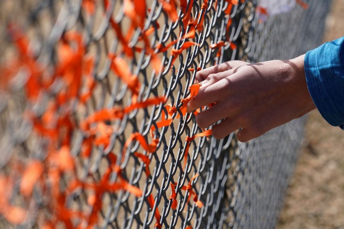 Columbine High School student Andrew Pavicich ties a memorial ribbon on the fence outside the school during the national school walkout to honour the 17 students and staff members killed at Marjory Stoneman Douglas High School in Parkland, Florida, i