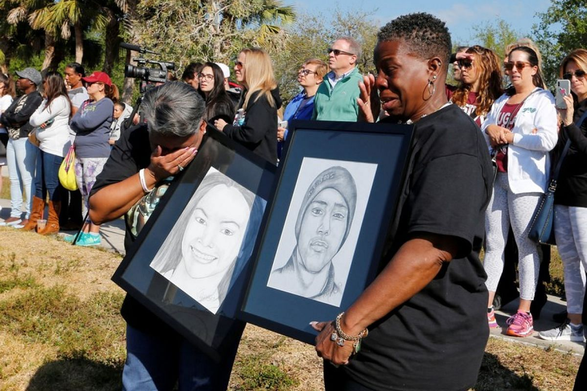 Pat Gibson holds a picture of Meadow Pollack and Valerie Davis holds a picture of Joaquin Oliver, students who died at Marjory Stoneman Douglas High School, during a national school walkout to honour the 17 students and staff members killed at the sc