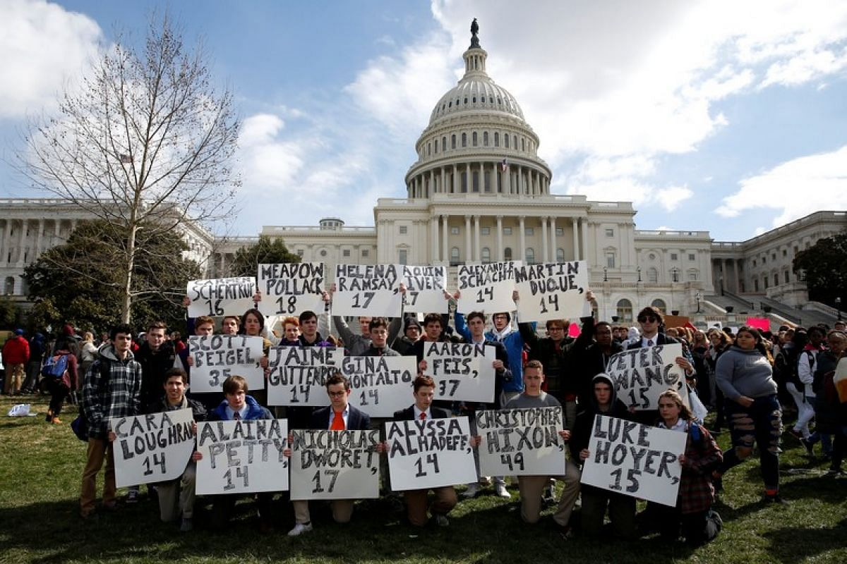 Students from Gonzaga College High School in Washington, DC, hold up signs with the names of those killed in the Florida school shooting during a protest for stricter gun control during a walkout by students at the US Capitol in Washington on March 1