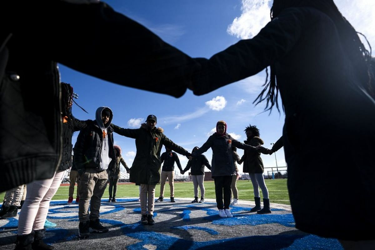 Eastern High School students walk out of class and assemble on their football field for the National School Walkout, a nation-wide protest against gun violence, in Washington, DC on March 14, 2018.