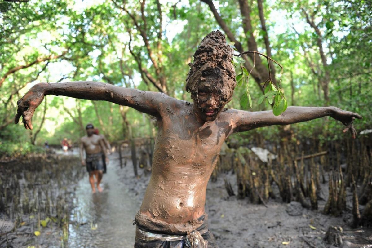 A Balinese boy puts mud on his body during a traditional mud bath known as Mebuug-buugan, in Kedonganan village on Indonesia's resort island of Bali on March 18, 2018.