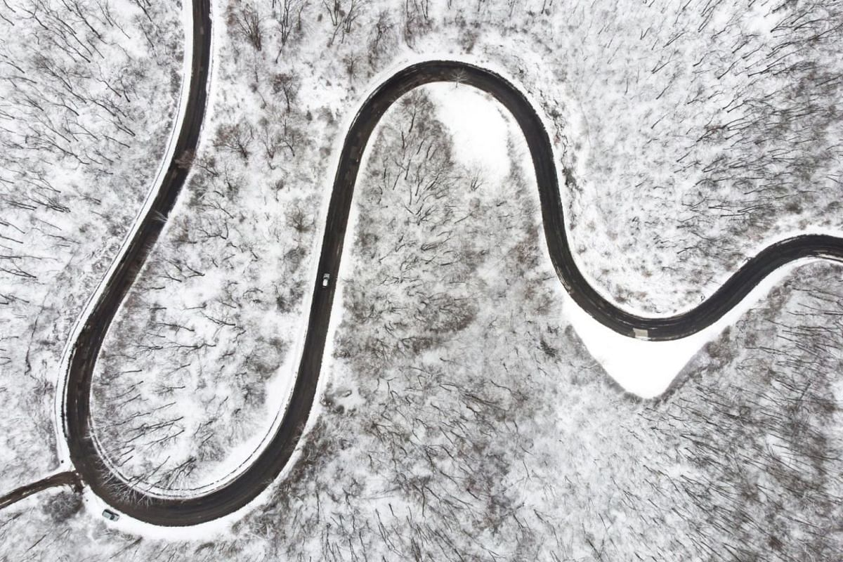 An aerial photo shows a motorist driving on a road that leads through the snow-corvered forests of the Pilis Mountain near Pilisszentlaszlo, 30 km north of Budapest, Hungary, on March 18, 2018.