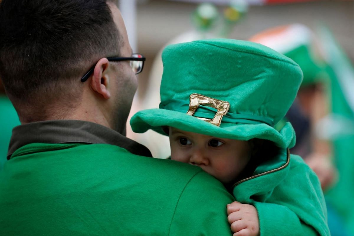 A participant carries a baby while attending the St Patrick's Weekend Parade in Valletta, Malta, on March 18, 2018.