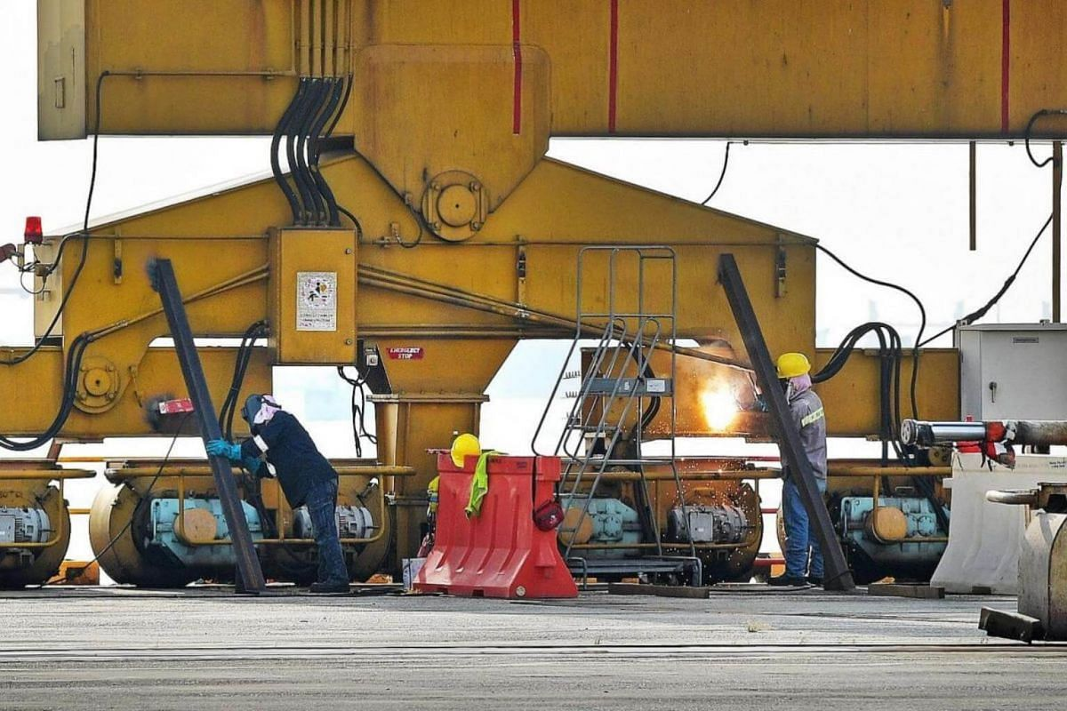 Workers carrying out hot work on a quay crane.