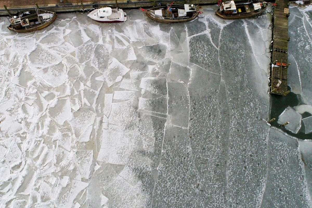 This aerial picture taken with a drone on March 21, 2018, shows fisher boats caught in the ice at the harbour of Stahlbrode, northeastern Germany.