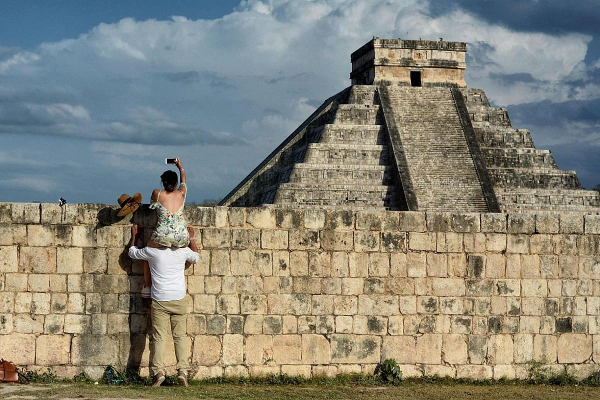 A woman sitting on a man's shoulder while taking a picture of the Kukulcan Pyramid at the Mayan archaeological site of Chichen Itza in Yucatan State, Mexico, during the celebration of the spring equinox on March 21, 2018.