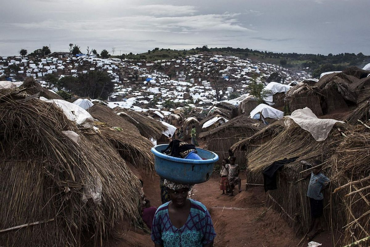 A Congolese woman walks through a camp for Internally Displaced Persons on March 20, 2018, in Kalemie, Democratic Republic of the Congo.