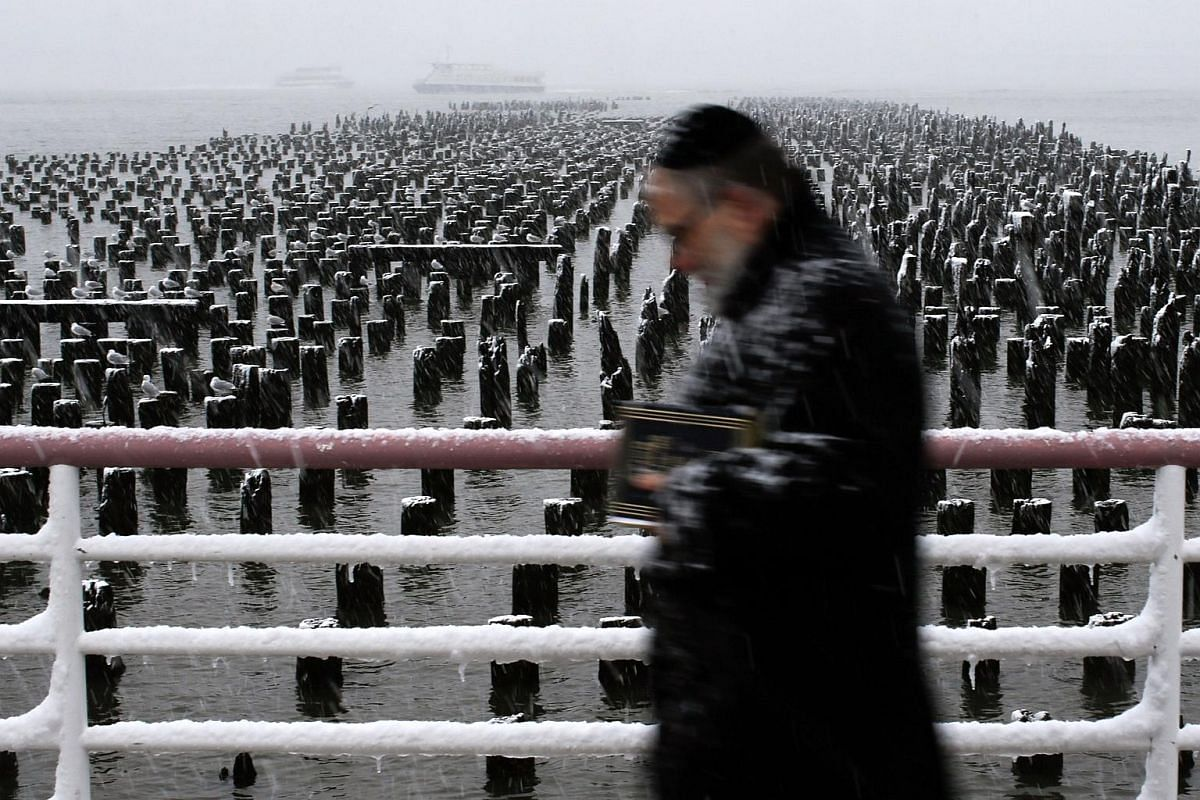 A man walks along the Hudson River during a snow storm on March 21, 2018 in Jersey City, New Jersey.