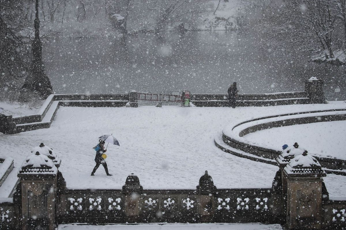 People walk near The Lake in Central Park during a snowstorm, on March 21, 2018 in New York City.