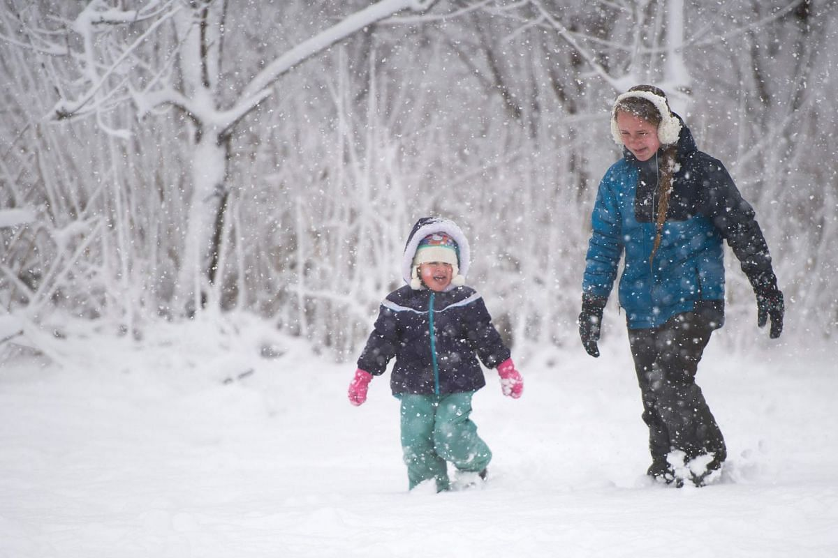 Two young girls walk through the snow in Centreville, Maryland on March 21, 2018.