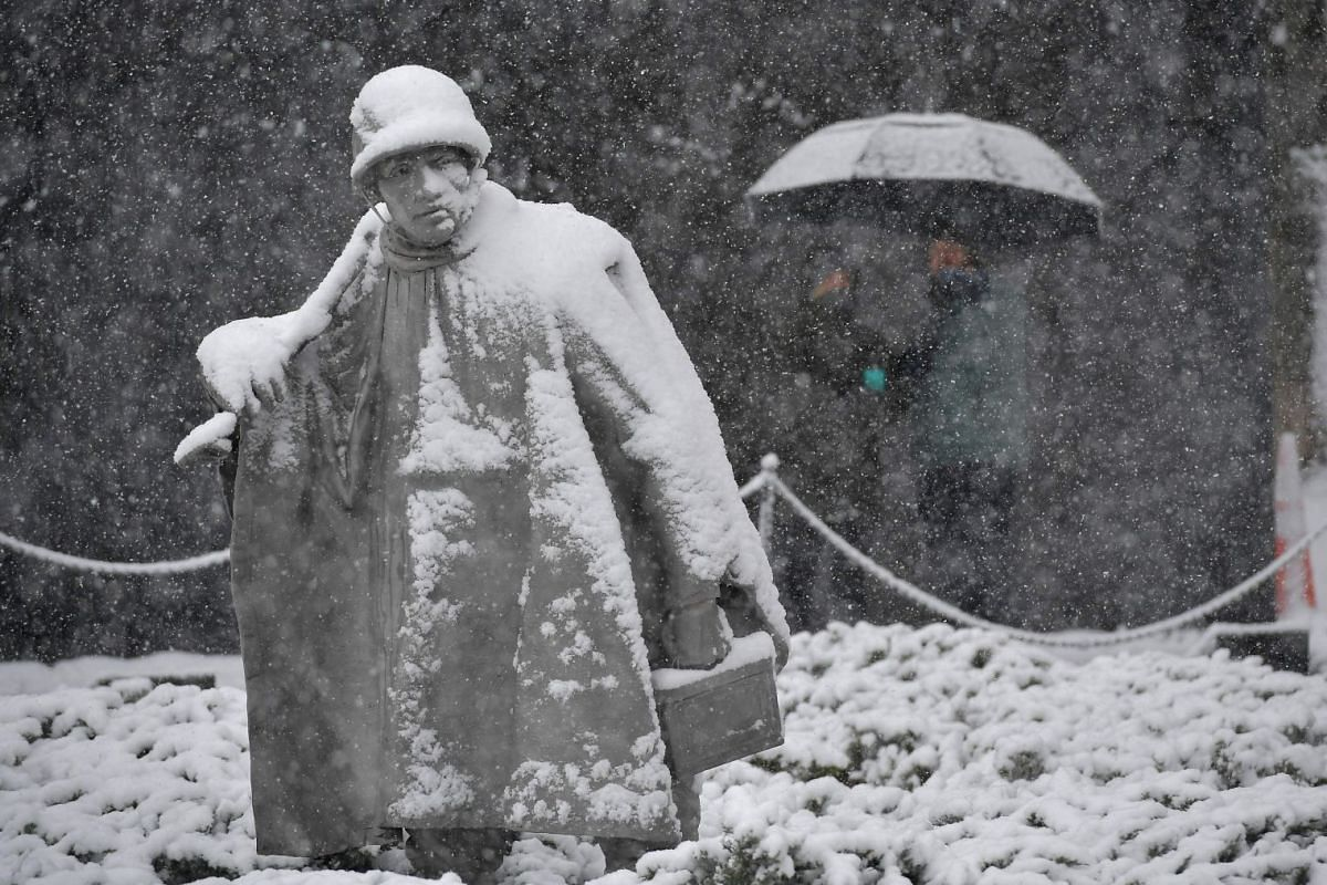 Tourists visit the Korean War Memorial during a snow storm in Washington, DC, on March 21, 2018.
