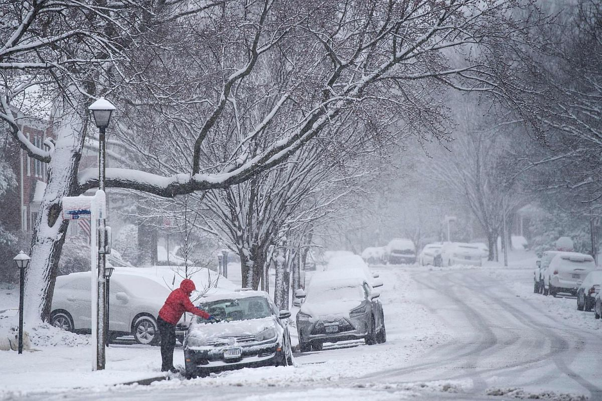 A woman cleans the front of her car in the Fairlington neighbourhood on March 21, 2018, in Arlington, Virginia.