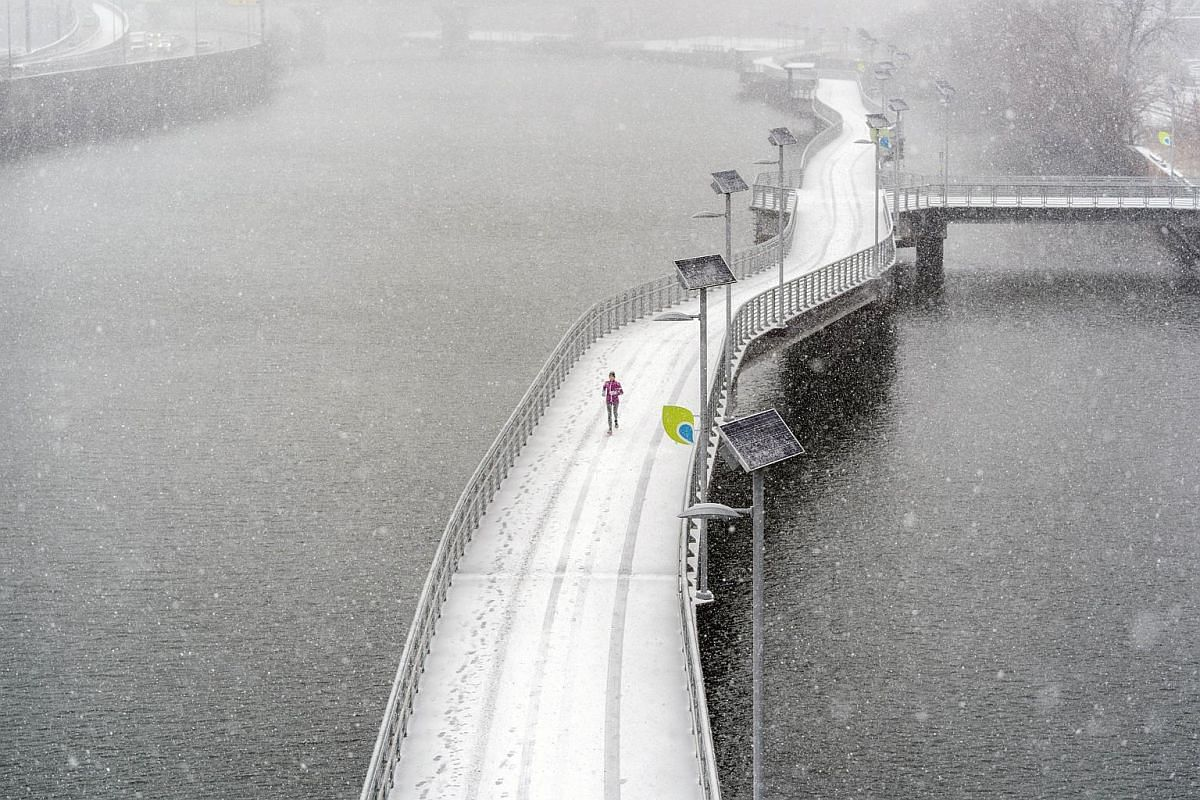A person runs through snow and high winds along the Schuylkill River on March 21, 2018 in Philadelphia, Pennsylvania.