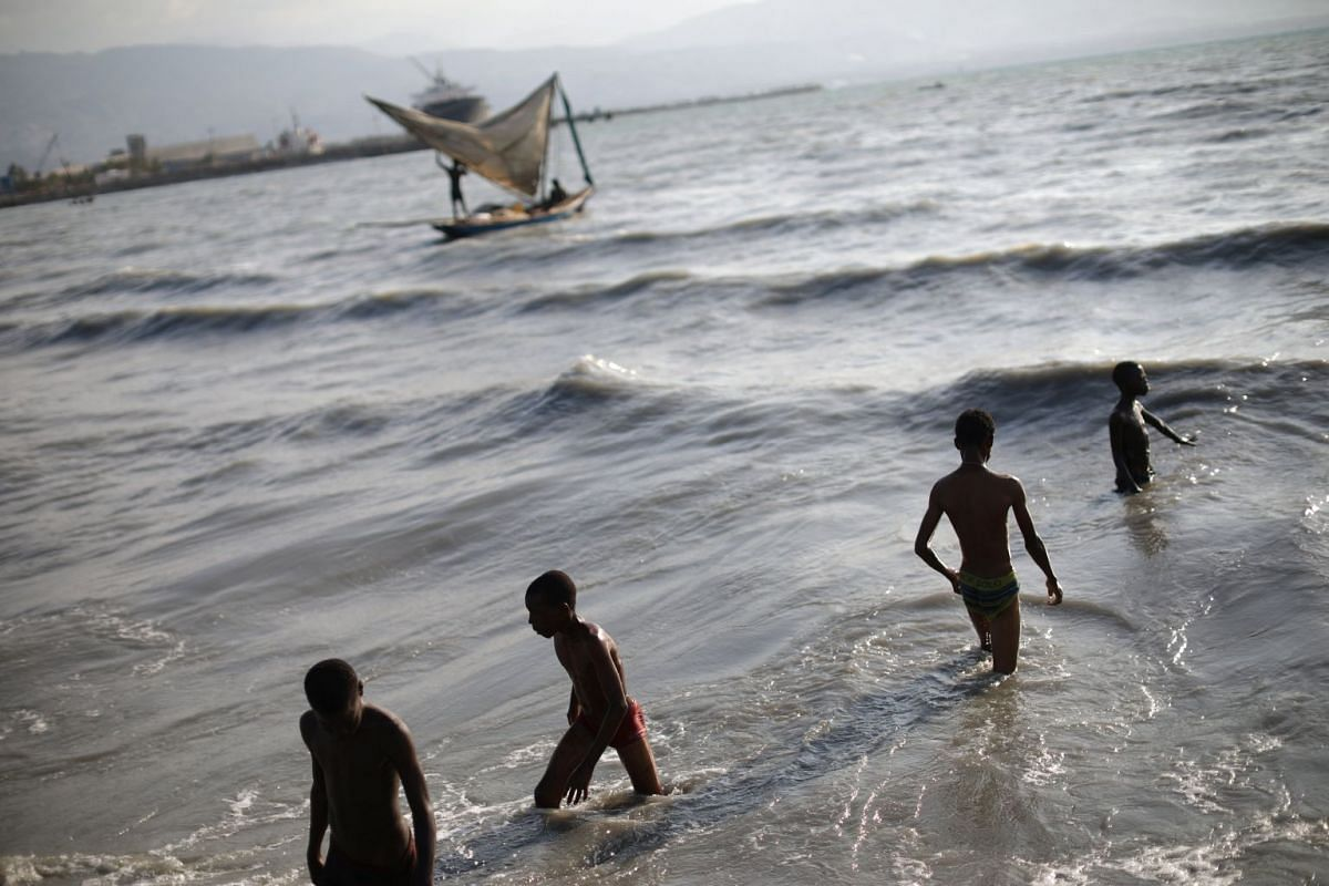 Children play in the water at the pier of Cite Soleil, Port-au-Prince, Haiti on March 22, 2018.