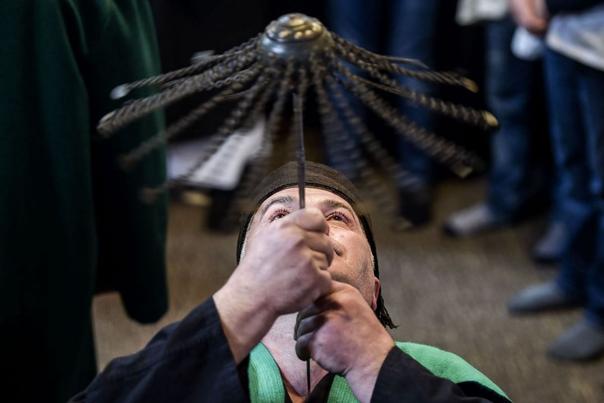 A Kosovo dervish, adept of Sufism, a mystical form of Islam, pierces his neck with a needle during a ceremony in a prayer room in Prizren on March 22, 2018.