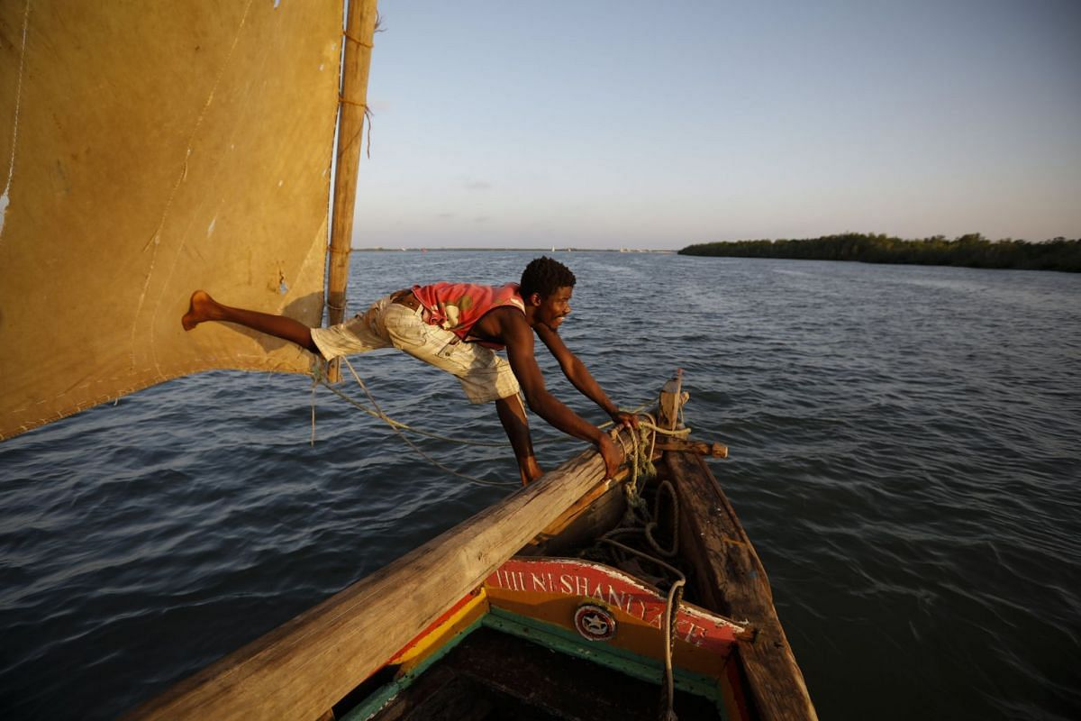 A man adjusts a mast aboard a dhow boat carrying tourists as it sails during the sunset off the coast of Lamu Island in south eastern Kenya, on March 22, 2018, World Water Day.