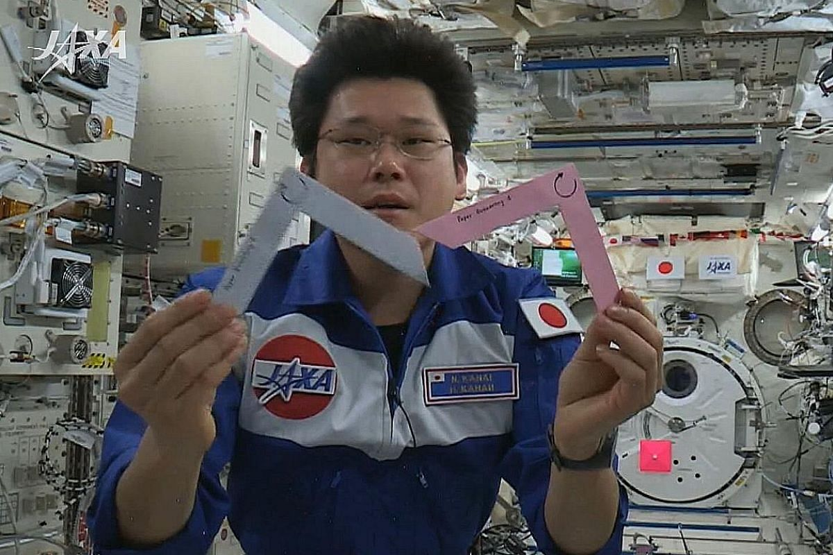 """Dr Norishige Kanai performing the boomerang experiment conceived by NUS High School of Mathematics and Science students, on board Japan's module at the International Space Station known as Kibo, or """"hope"""" in Japanese. The students had asked: Will a boomer"""