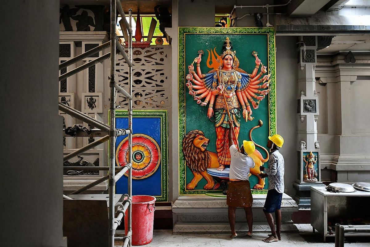 Mr Viswanathan Karunanithi (left), 47, and Mr Karuppaiyan Chidambara-nathan (right), 48, two of the 20 skilled temple artisans from India, painting motifs representing Indian astrology signs on the ceiling above the Garudar sanctum. The men are worki