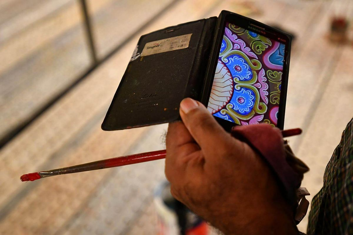 An artisan looks at a photo of a painting on his handphone to confirm colours used at Sri Srinivasa Perumal Temple on Jan 10, 2018.