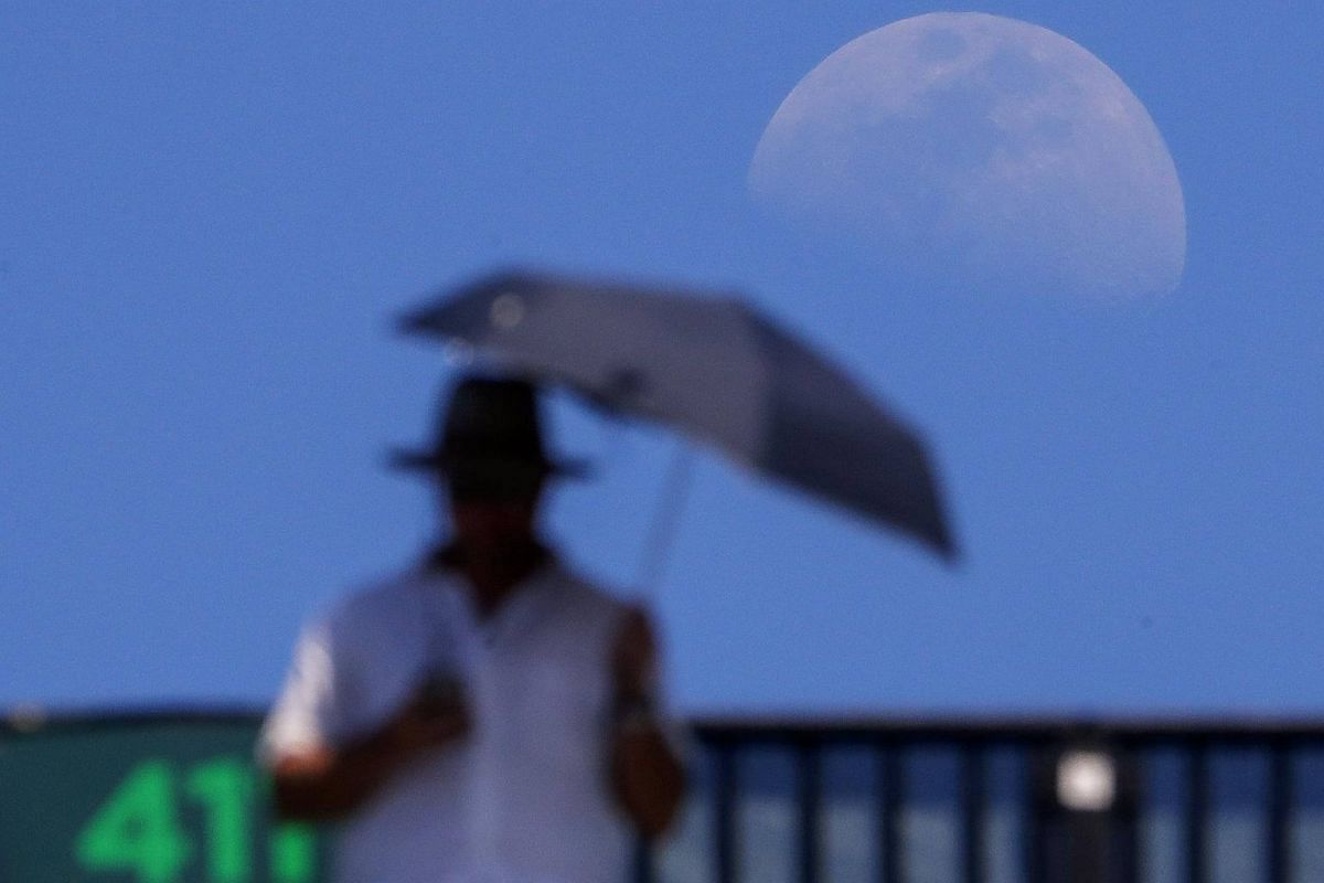 The moon rises behind a tennis fan as Venus Williams plays Kiki Bertens during their third round match at the Miami Open tennis tournament at Key Biscayne, Florida, on March 25, 2018.